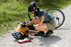 Germany, Bavaria, Oberland, Woman giving aid to fallen biker